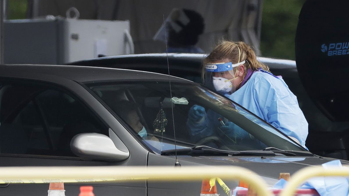 A health care worker prepares to test a driver in line at a drive-thru COVID-19 testing site...