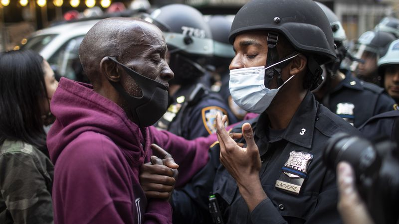 FILE - In this June 2, 2020 file photo, a protester and a police officer shake hands in the...