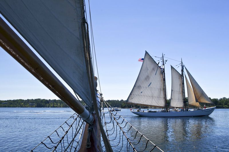 The Schooner Bowdoin, launched by arctic explorer Donald MacMillan in 1921, sails by the bow of...