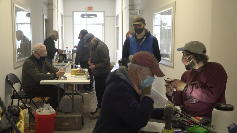 Volunteers work with residents to repair both clothing and appliances at the café.