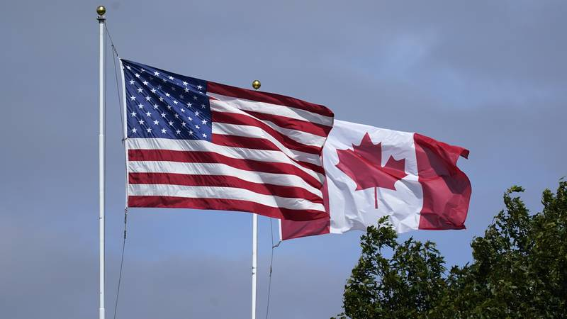 U.S. and Canadian flags fly together at the border at the Peace Arch Historical State Park,...