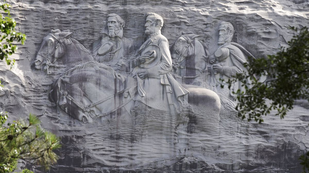 FILE - This June 23, 2015, file photo shows a carving depicting Confederate Civil War figures Stonewall Jackson, Robert E. Lee and Jefferson Davis, in Stone Mountain, Ga. The sculpture is America's largest Confederate memorial. The suburban Atlanta park that's home to the massive carving of Confederate leaders says it will close its gates Saturday, Aug. 15, 2020, in the face of a planned right-wing rally.