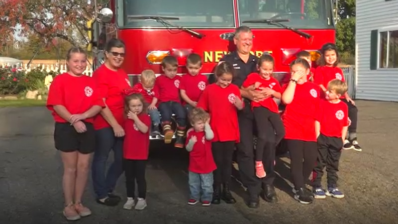 """Fireman Tim"" Vashon poses with Kidsville pre-school students and Kidsville owner, Laurie Garner."