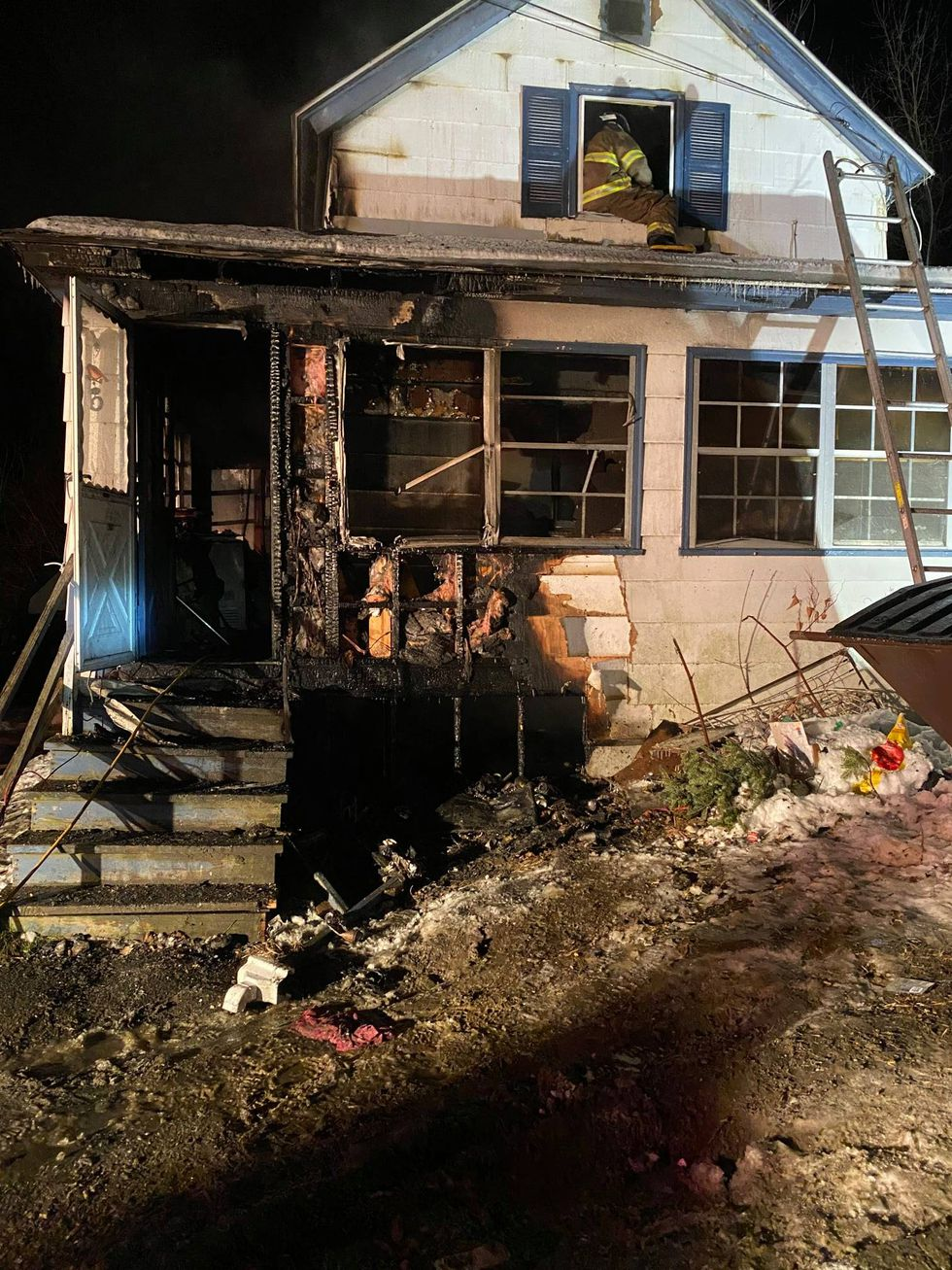 Four children and three adults climb out of a back window to escape their burning home Monday...