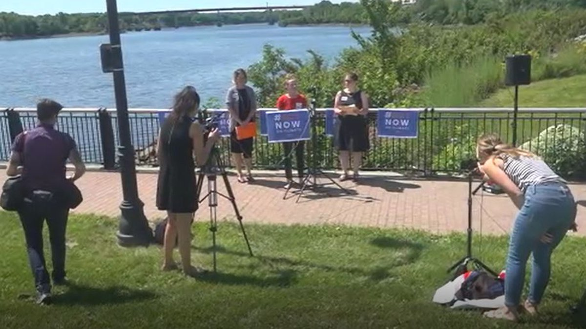 A group of elected officials and climate justice advocates gathering on the Bangor waterfront...