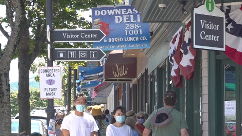 Masked tourists walk down Main Street in Bar Harbor.