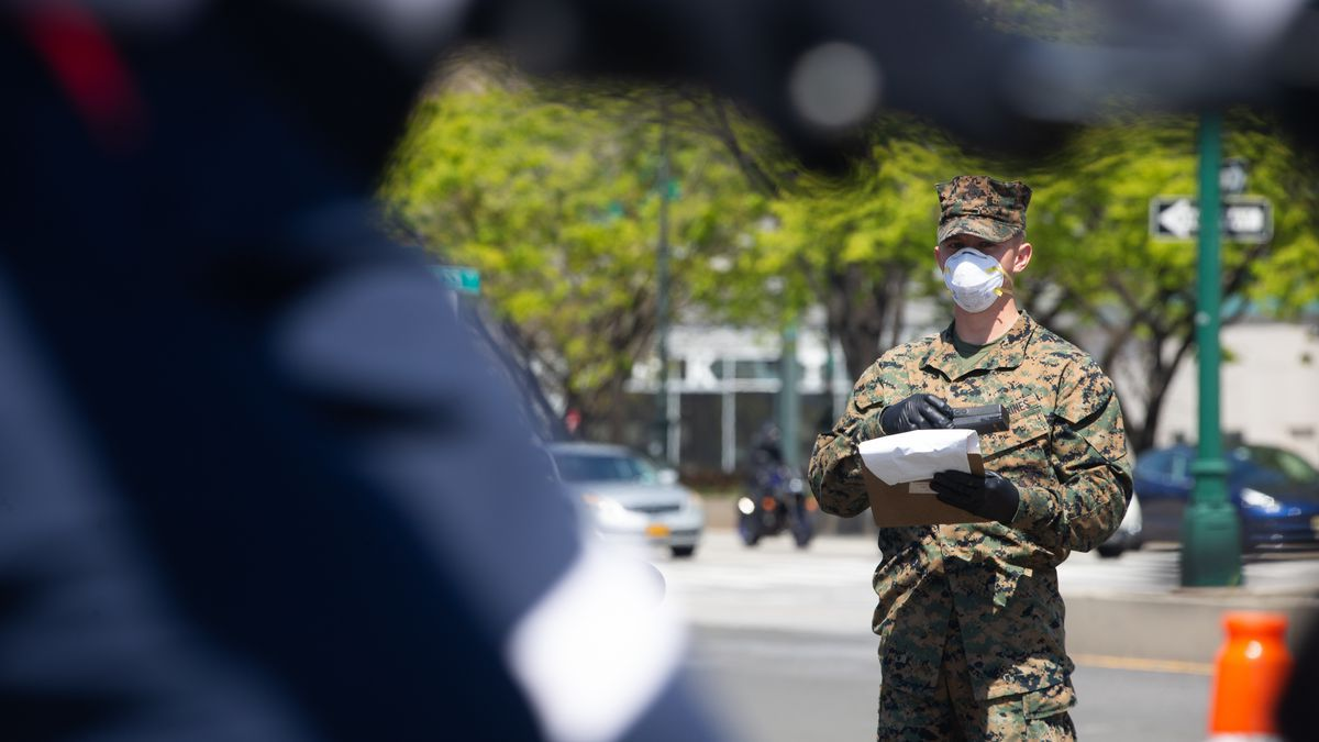 Lance Cpl. Wayne Parsons, a rifleman with Lima Company, 3rd Battalion, 2nd Marines, Task Force New York, observes pedestrians while providing security for the USNS Comfort (T-AH 20) during COVID-19 relief efforts in New York City on April 19, 2020.(Source: Sgt. Stormy Mendez/U.S. Marine Corps)