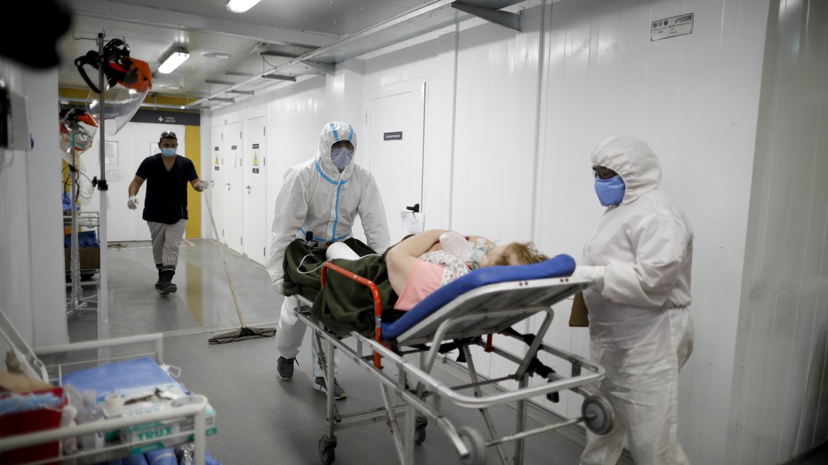 Health workers bring a COVID-19 patient on a stretcher into a hospital.