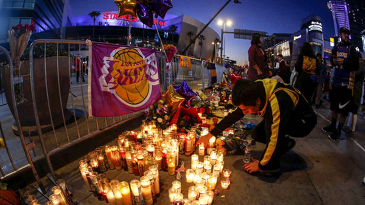 A fan places a candle at a memorial for Kobe Bryant near Staples Center, Tuesday, Jan. 28, 2020, in Los Angeles. Bryant, the 18-time NBA All-Star who won five championships and became one of the greatest basketball players of his generation during a 20-year career with the Los Angeles Lakers, died in a helicopter crash Sunday. (AP Photo/Ringo H.W. Chiu)