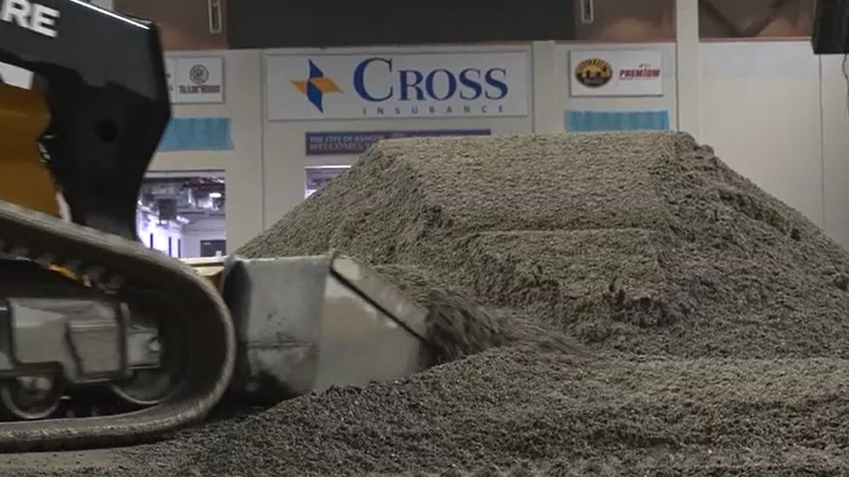 Tons of dirt is moved into place on the floor of the Cross Center to prepare for this weekend's...