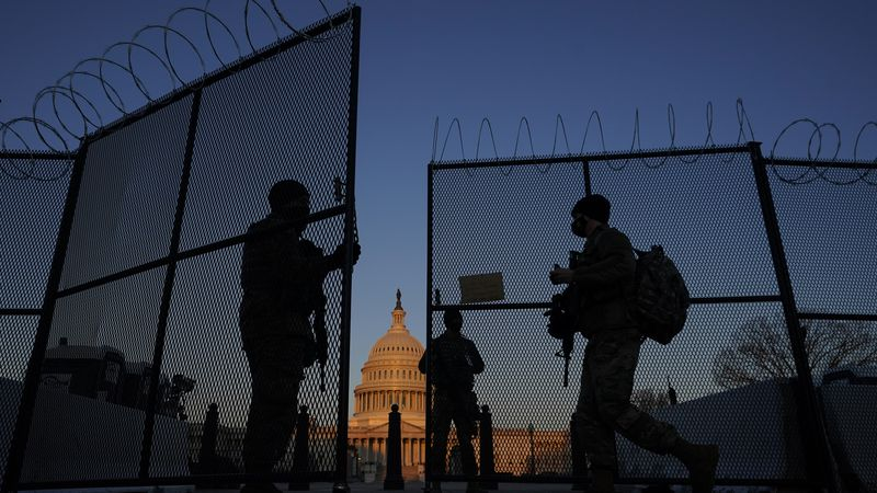 FILE - In this March 8, 2021, file photo, members of the National Guard open a gate in the...