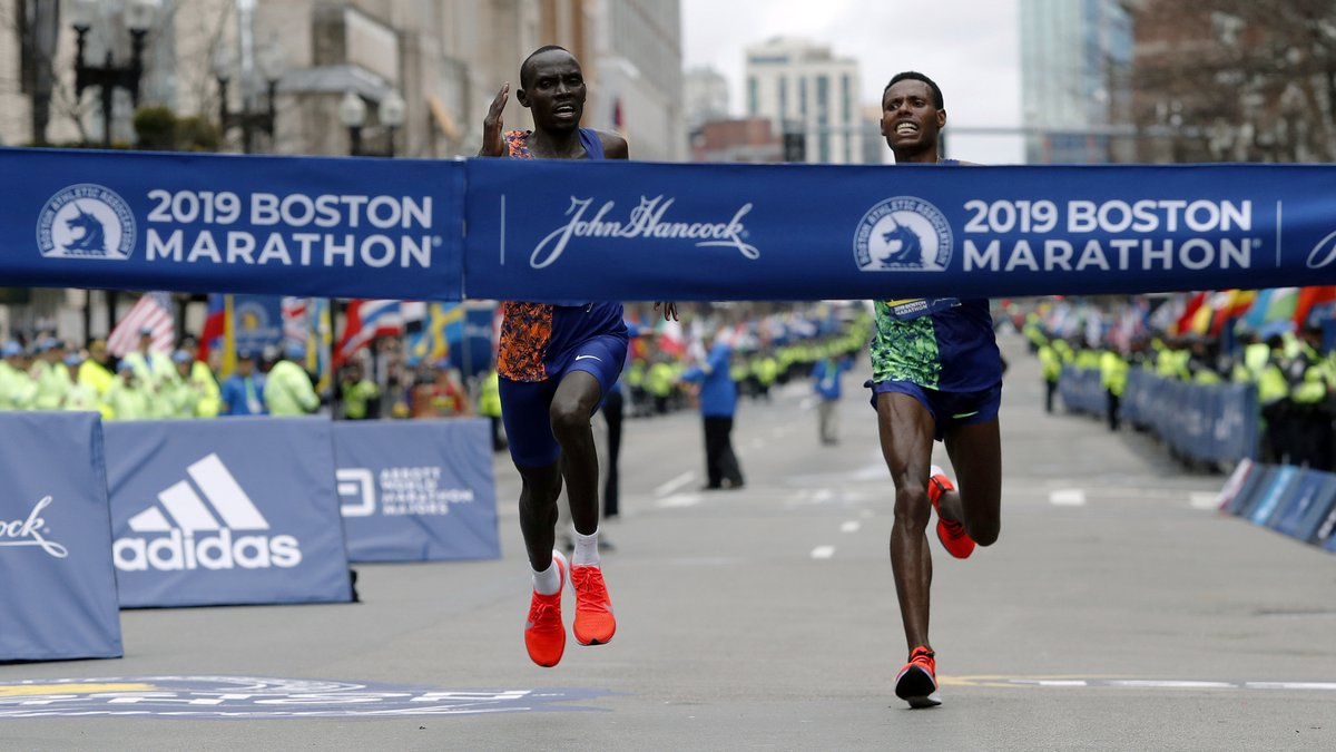 FILE - Lawrence Cherono, left, of Kenya, runs to the finish line to win the 123rd Boston...