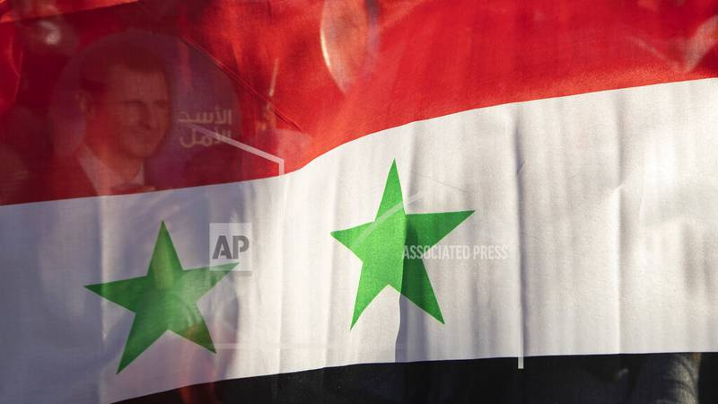 FILE - In this May 23, 2021, file photo, the Syria national flag is displayed at a gathering at...