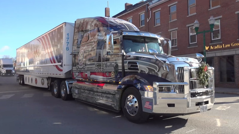 A Wreaths Across America truck carrying wreaths to Arlington National Cemetery rolls through...