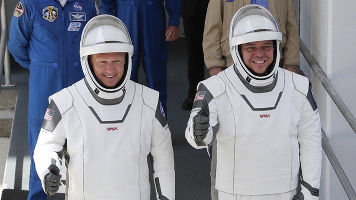NASA astronauts Douglas Hurley, left, and Robert Behnken walk out of the Neil A. Armstrong...